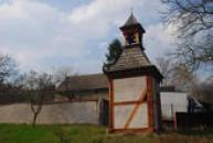 Dřevěná zvonice se šindelovou střechou.