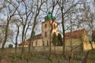 Kostel Všech Svatých ukrytý za stromy.