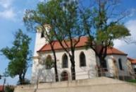 Kostel Narození sv. Jana Křtitele schován za stromy.