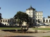 Kašna v parku a zámecké budovy.