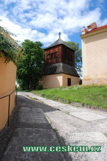 Dřevěná zvonice u kostela v Řisutech.