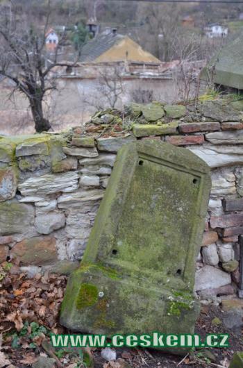 Dávný náhrobek u hřbitovní zdi.