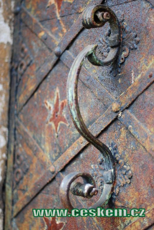 Práce dávného kováře na dveřích kostela.