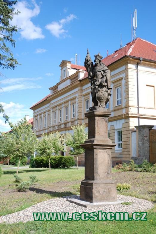 Barokní socha před budovou školy.