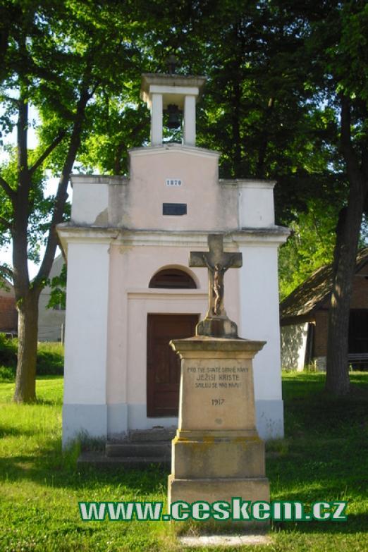 Křížek před kaplí na návsi.